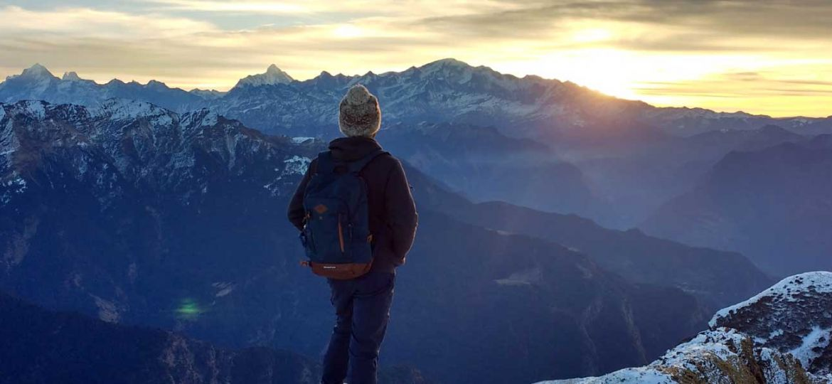 Solo travel tips - Shows a guy looking out at the mountains at sunset