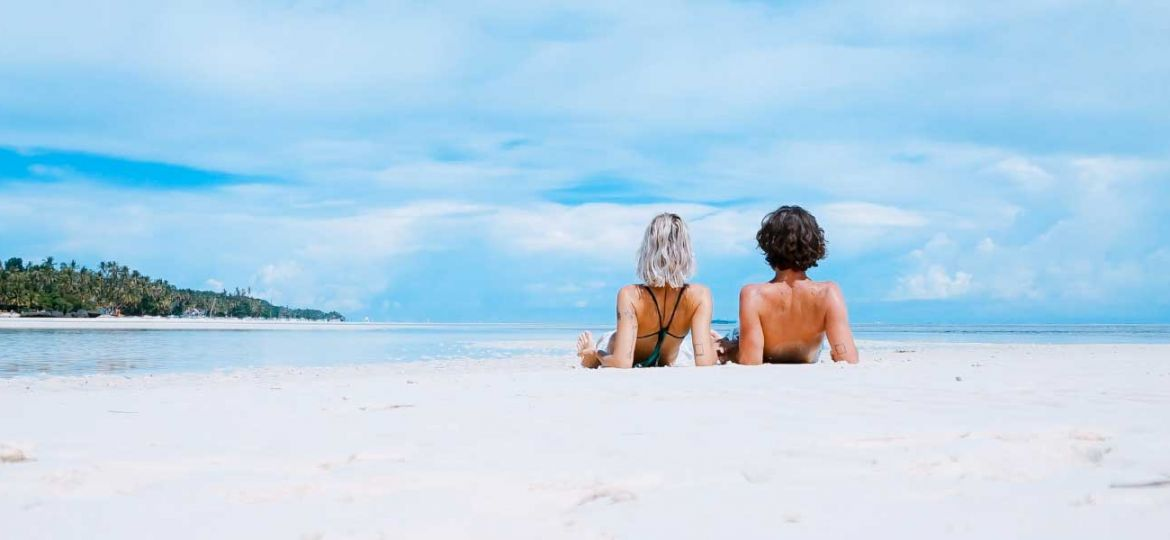 Budget honeymoon destinations and tips - Shows a couple on a remote beach