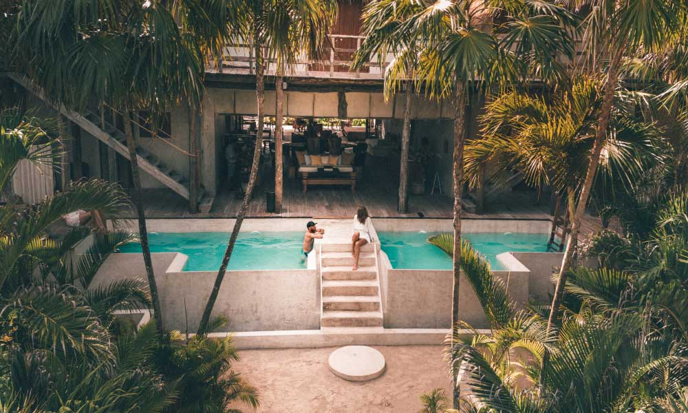 Shows a couple in a resort swimming pool - Honeymoon on a budget