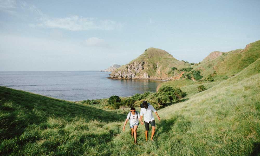 Honeymoon money saving tips - Shows a couple hiking a hill