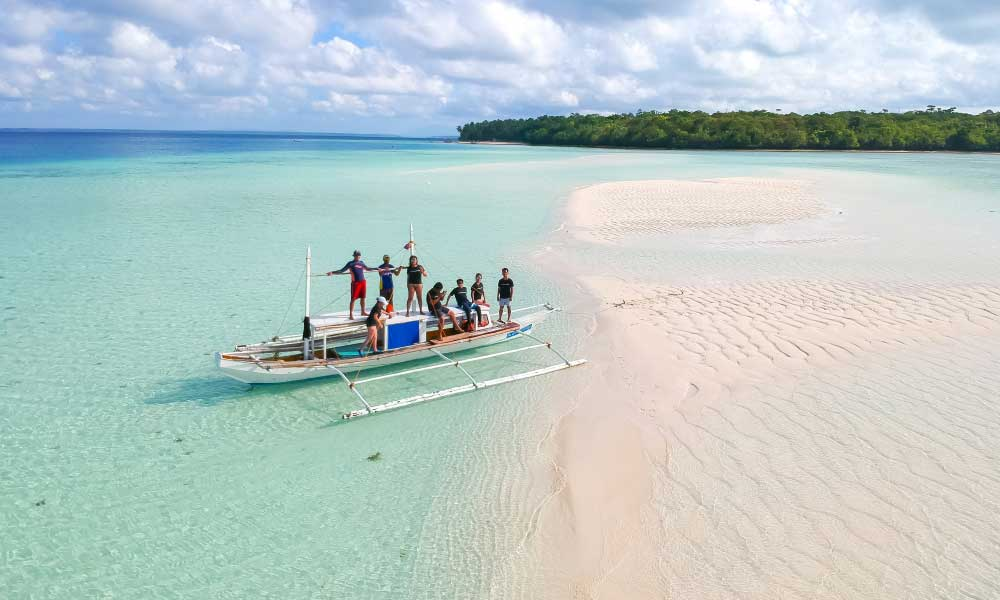 Shows the crew on board a boat on a sand bar - How to get to Balabac Islands