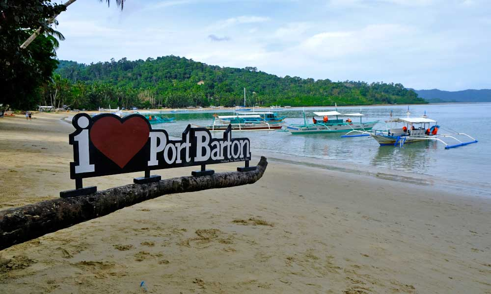 How to get to Port Barton - Shows beach with boats and an I love Port Barton sign