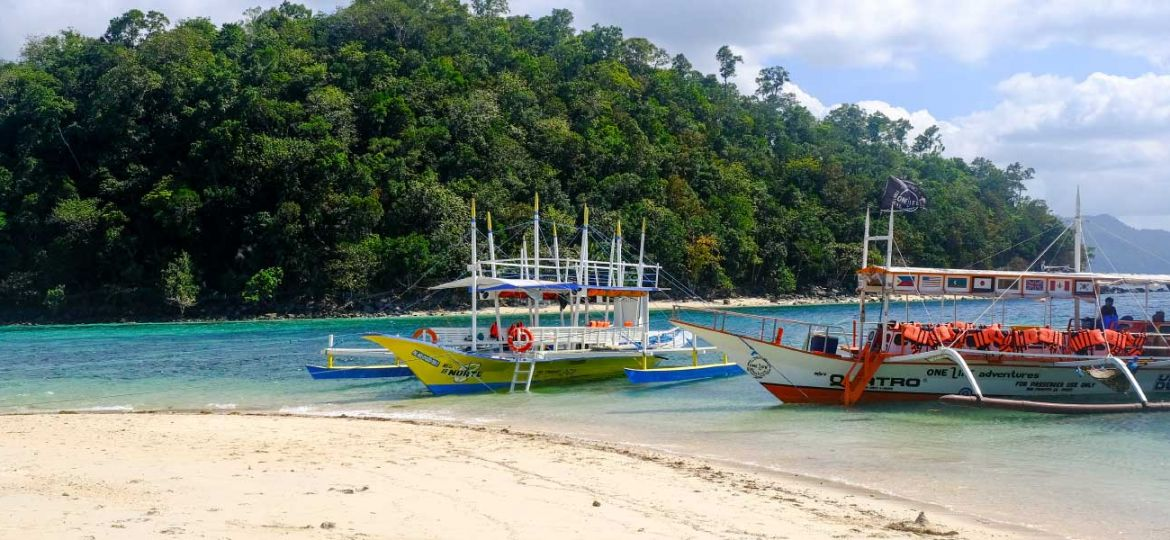 Where to stay in Palawan - Shows two boats on a beach