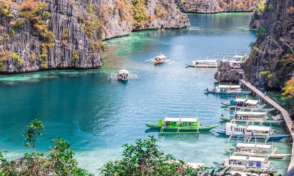 Where to stay in Coron - Shows a lagoon with boats and limestone cliffs