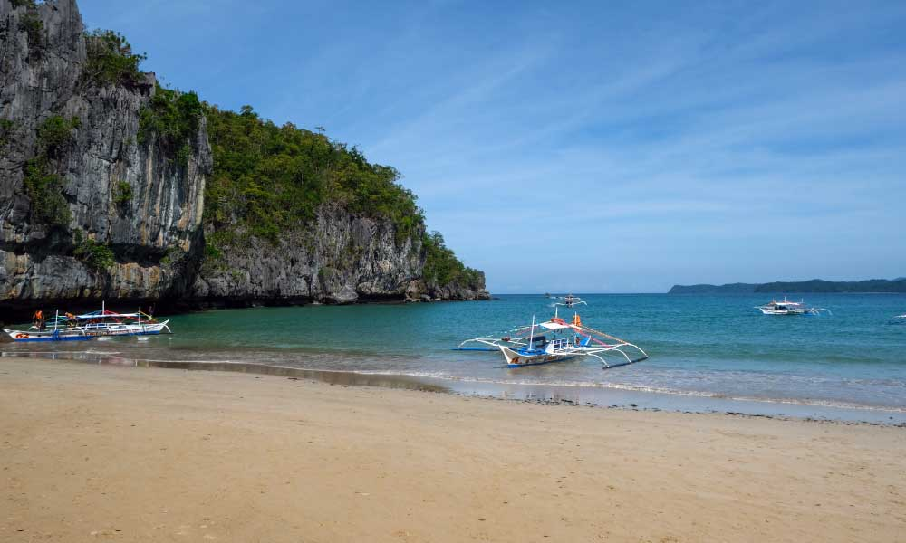 Where to stay in Puerto Princesa - Shows a quiet beach with a Filipino boat