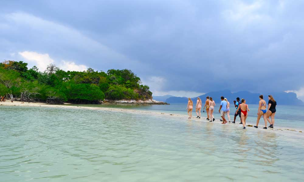 One Life Adventures Philippines tour - Shows the One Life Tour group walking over a sand bar