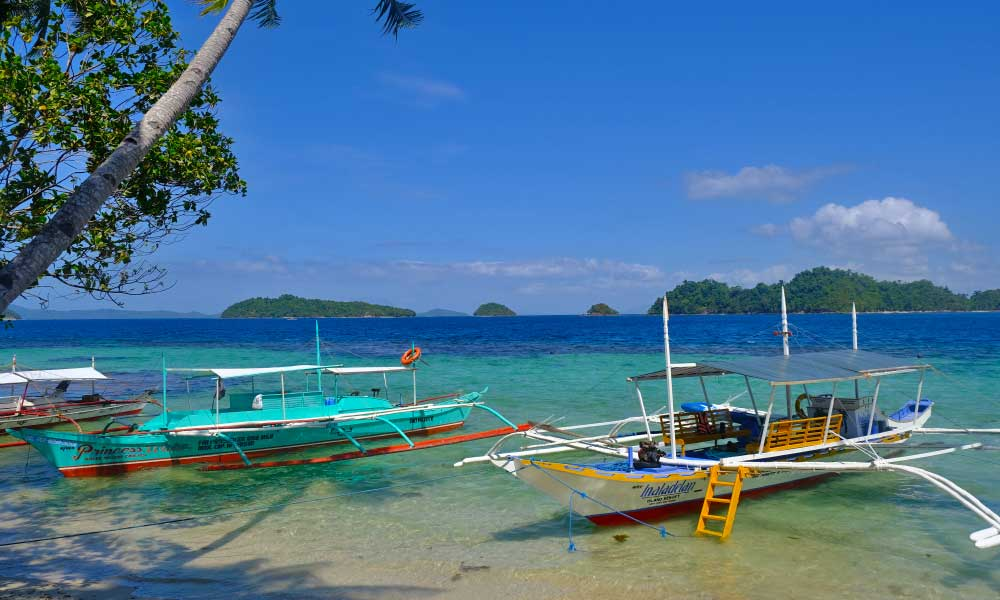 Shows two Filipino boats on the shore of a beach