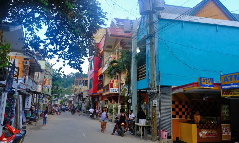 Depicts El Nido town streets and colourful buildings
