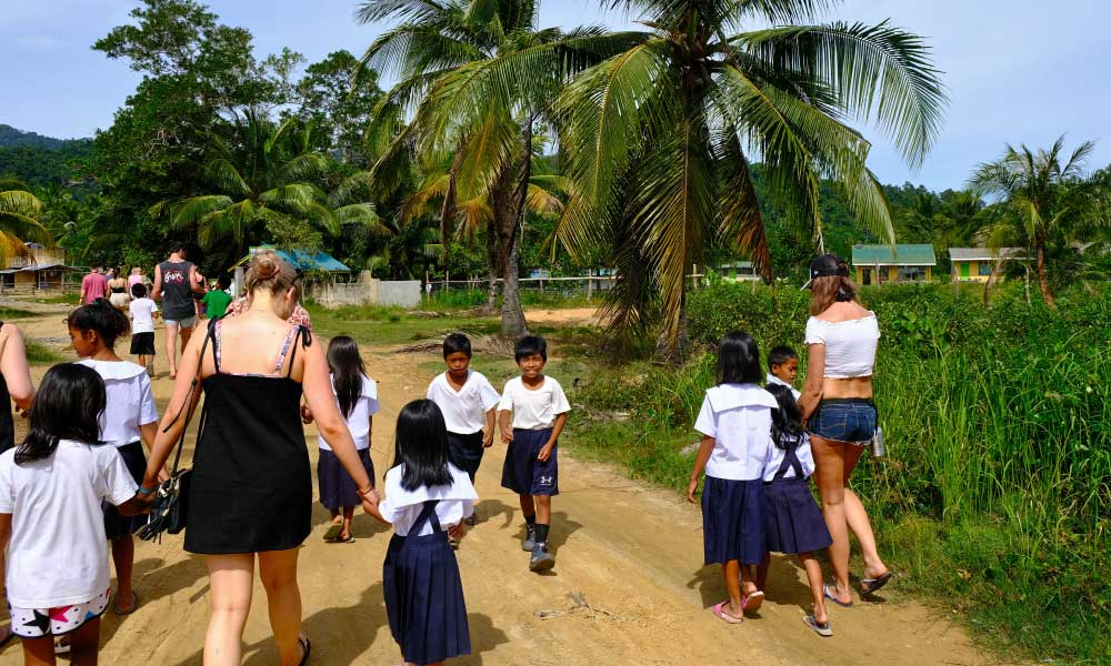 One Life Adventures Philippines tour - Shows children greeting a tour group at their school