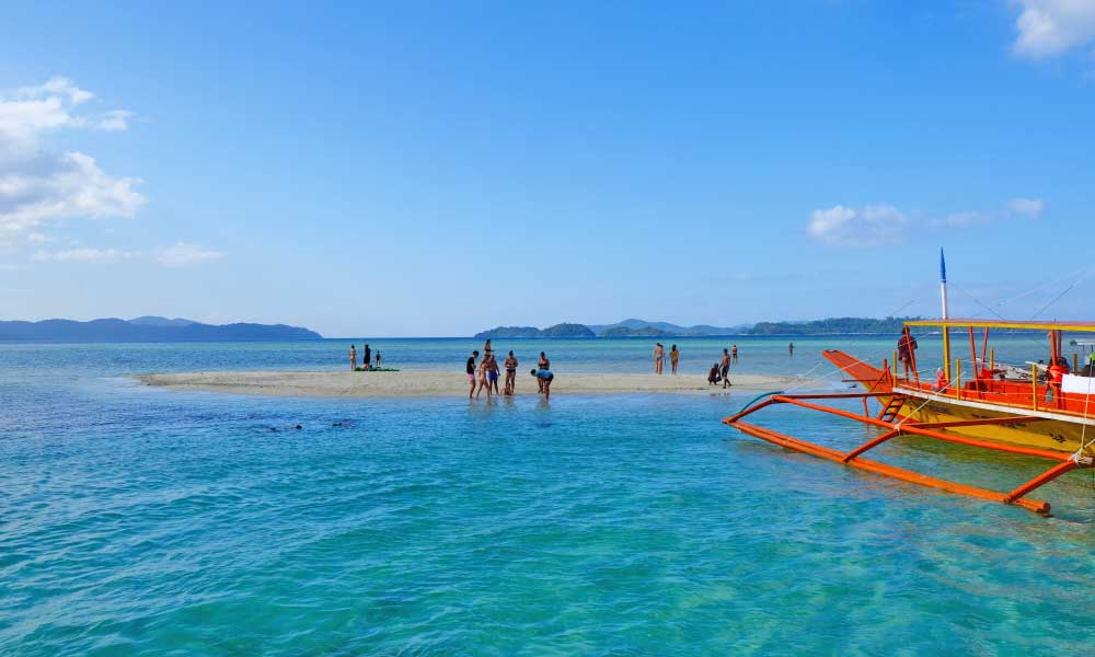 One Life Adventures Philippines tour - Shows a group of tourists on a sand bar in the ocean