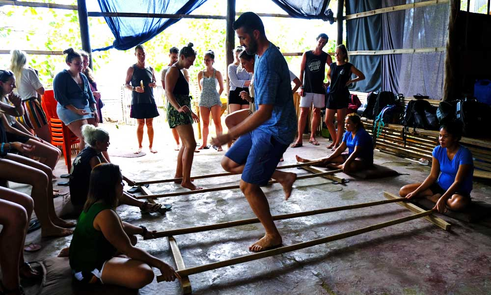 Shows a man doing a traditional Filipino bamboo stick dance