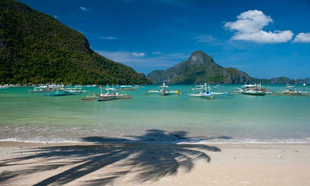 Depicts El Nido town beach and a collection of docked boats One Life Adventures Philippines tour