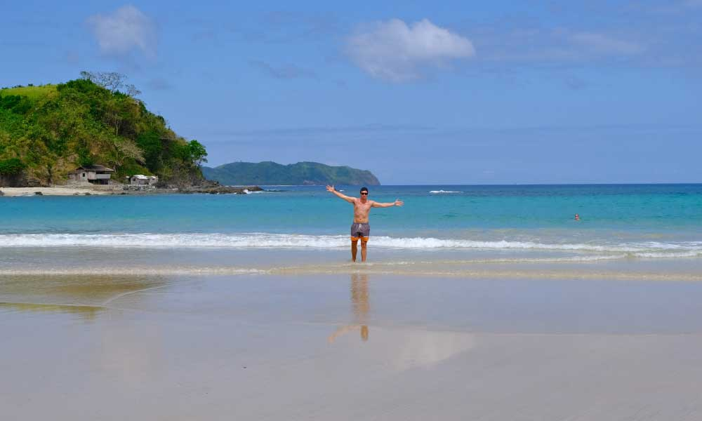 A view of Nacpan Beach with me waving my arms in the air
