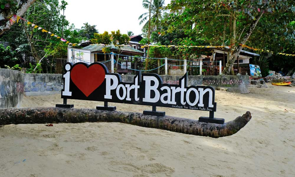 Shows Port Barton welcome sign on the beach