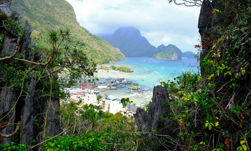 Shows a stunning view of El Nido town and beach below