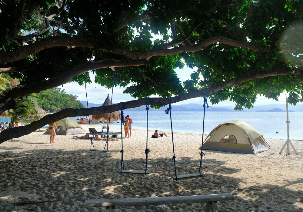 Shows German Island in Port Barton with beach swings and tents