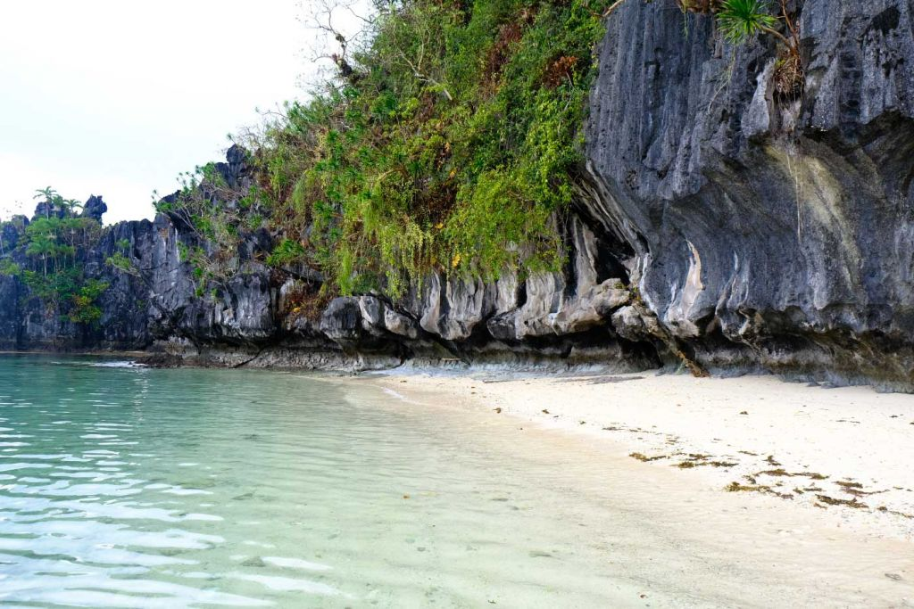 Island hopping in El Nido - Shows a remote beach with cliffs
