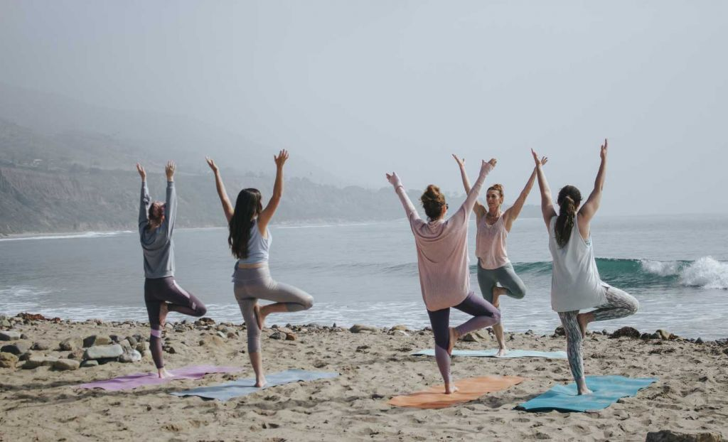 Group yoga on the beach with foggy weather