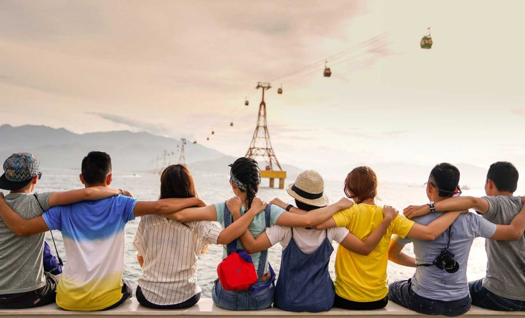 Shows a group of friends overlooking the ocean - Couples travel tips