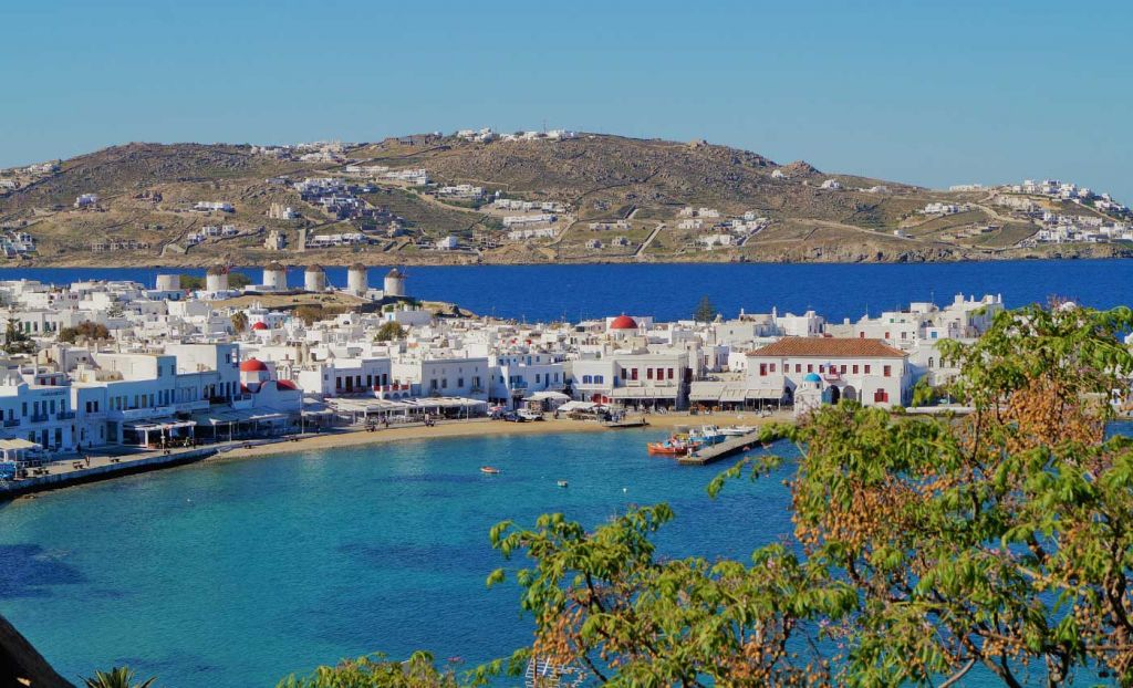 Best group holiday destinations - Beach and white buildings of Mykonos