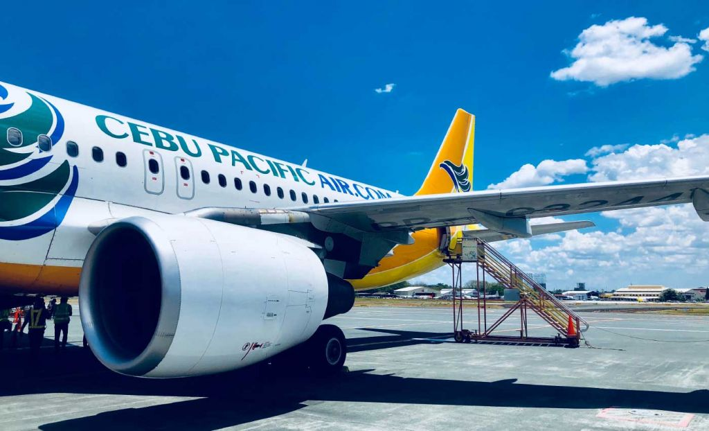 Shows a Cebu Pacific plane at the airport