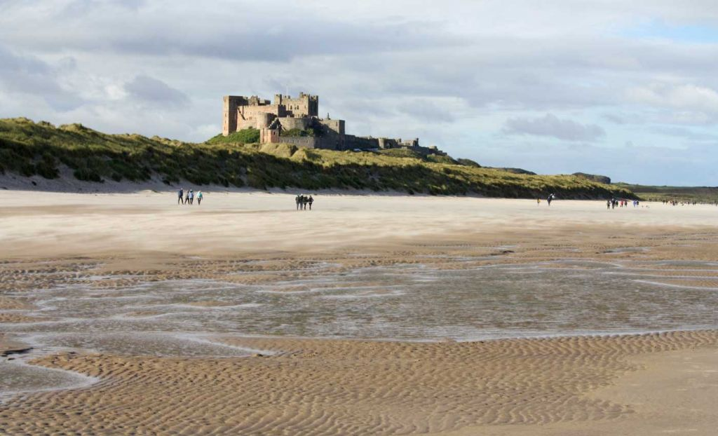 Cheap places to visit in the UK - View of Bamburgh Castle from the beach