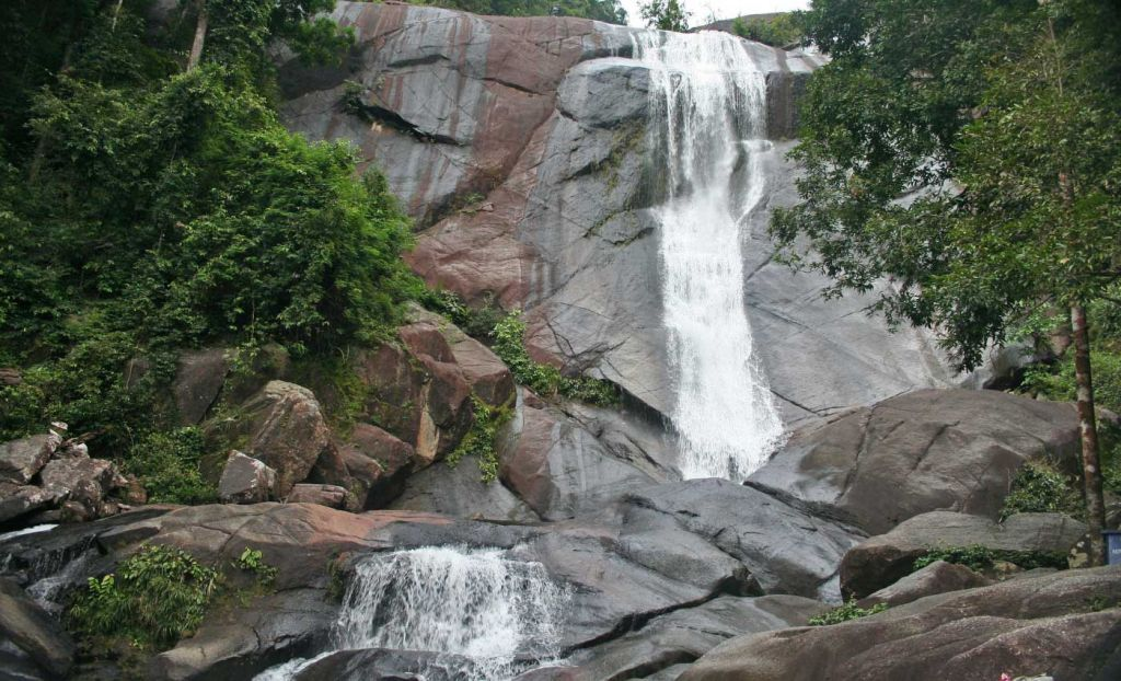 Shows Telaga Tujuh waterfalls and rocks below