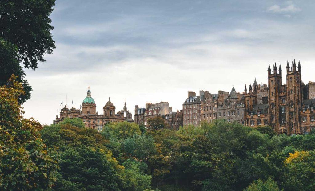 Old buildings of Edinburgh city centre alongside bushy trees