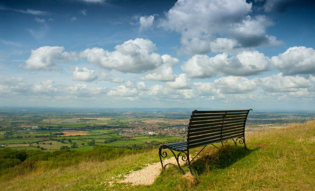 A park bench overlooking the countryside from Cleeve Hill
