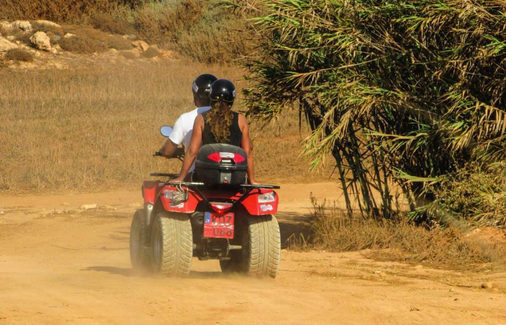 Shows a couple exploring on a quad bike