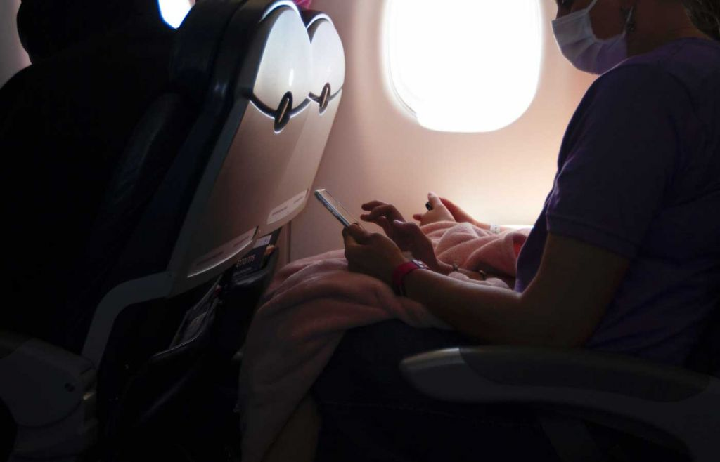 Travelling during the pandemic to Cyprus - Shows a person a plane with a mask