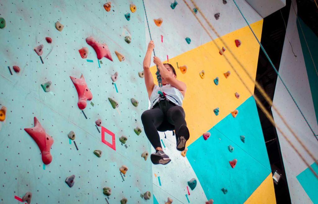 Shows a girl rock climbing indoors