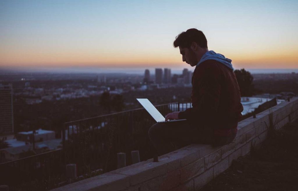A man researching on his laptop with a city skyline in the background