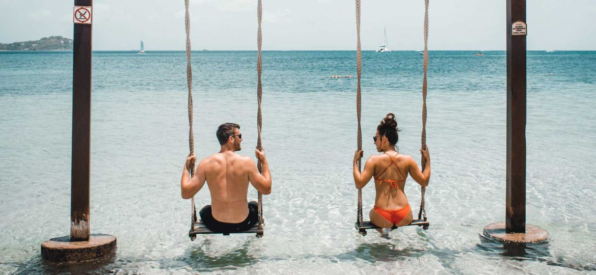 Holidays for young couples - Shows a couple on beach swings