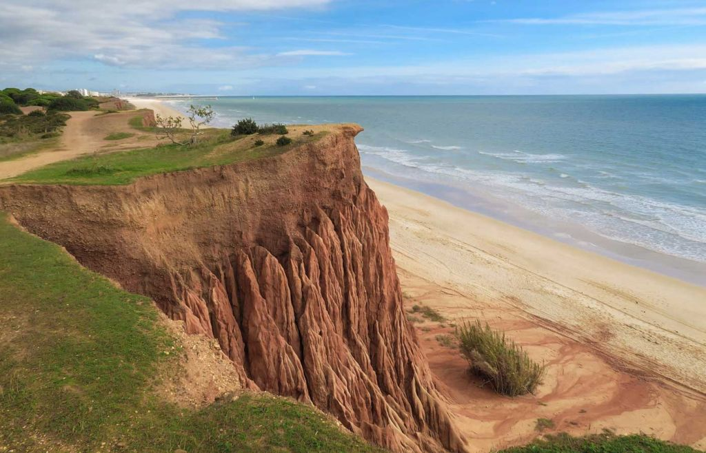Shows a tall cliff facing out to Falesia beach - Best Algarve beaches