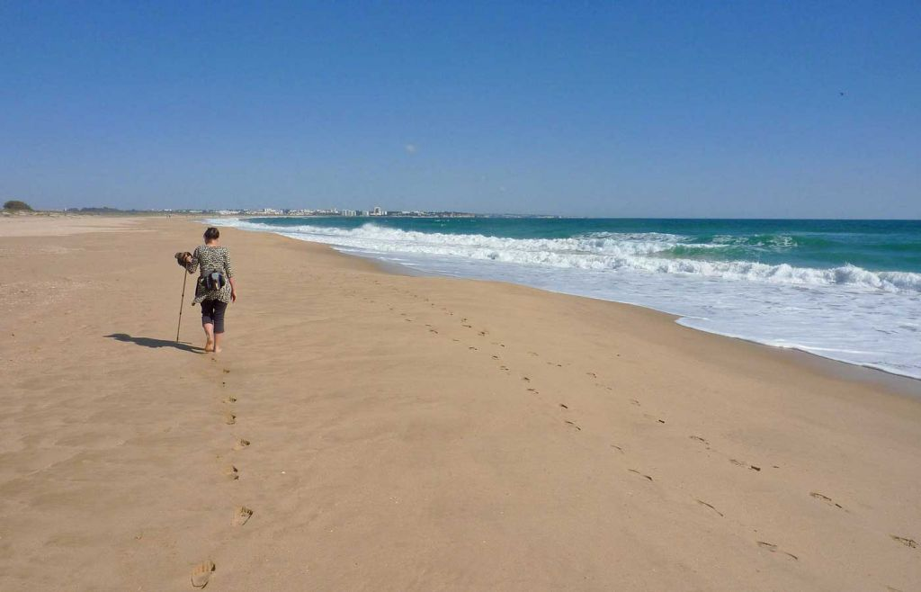 Woman walking across Meia Praia by the shore
